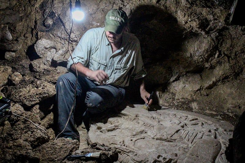 Tulane archaeologist Marcello A. Canuto sits beside the altar he and his team discovered in the jungles of northern Guatemala. (Photo courtesy of the National Museum of Archaeology and Ethnology in Guatemala City.