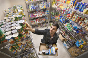 Photo caption: Graduate student Trey Delcambre organizes canned food donated to UL Lafayette's Campus Cupboard. The on-campus pantry opens Tuesday in the University's Intensive English Program building, 413 Brook Ave. (Photo credit: Doug Dugas / University of Louisiana at Lafayette).