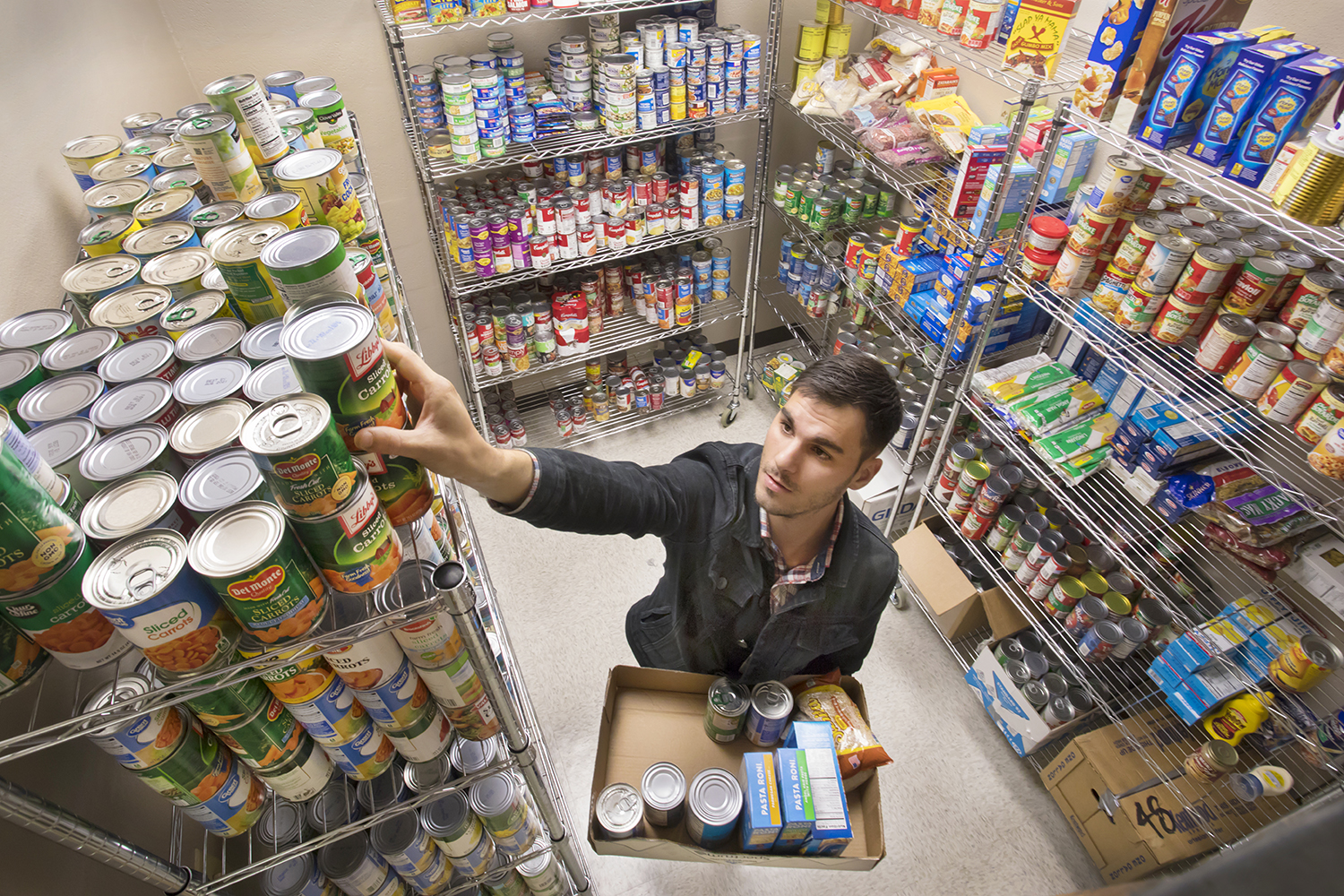 Photo caption:Graduate student Trey Delcambre organizes canned food donated to UL Lafayette's Campus Cupboard. The on-campus pantry opens Tuesday in the University's Intensive English Program building, 413 Brook Ave. (Photo credit:Doug Dugas / University of Louisiana at Lafayette).