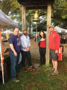 CODOFIL board member Michael Vincent, CODOFIL communications officer Matt Mick, CODOFIL community development specialist Maggie Perkins, and Lafayette Farmers and Artisans Market director Mark Hernandez ring the bell at the start of Saturday's market.