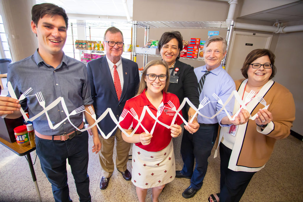 UL Lafayette's Campus Cupboard held a ribbon-cutting ceremony Thursday to mark its grand opening. From left are Trey Delcambre, a graduate student who manages the food pantry; Dr. Joseph Savoie, University president; Chandler Harris, Student Government Association president; Patricia Cottonham, vice president for Student Affairs; Dr. Pearson Cross, associate dean of the College of Liberal Arts; and Dr. Margarita Perez, dean of students. (Photo credit: Doug Dugas / University of Louisiana at Lafayette)