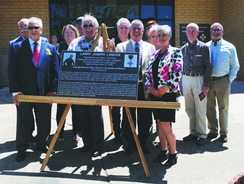 Alumni from the New Iberia Senior High School Class of 1969 surround the plaque honoring their fallen classmate, Specialist Fourth Class Larry Joseph Lancon, at the building dedication ceremony for the Lancon Soldier Centered Medical Home at Fort polk April 26, 2019.