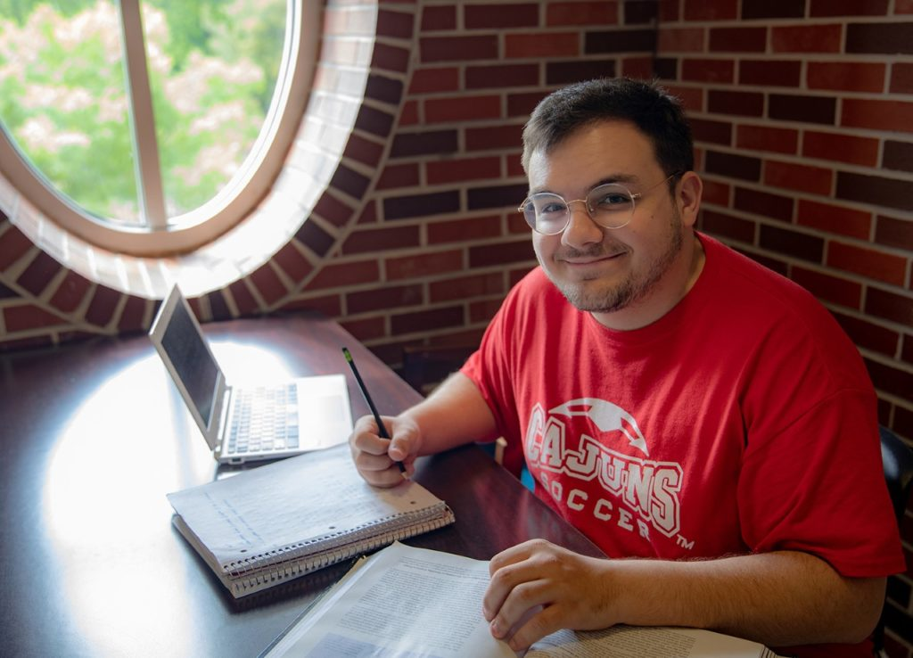 Photo caption: UL Lafayette accounting graduate Zach Wells in a familiar study spot, Moody Hall's second-floor atrium. (Photo credit: Rachel Keyes / University of Louisiana at Lafayette)
